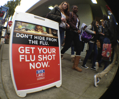 """Students walk past a sign outside a Rite Aid pharmacy which reads """"Get Your Flu Shots Now&quot 09 January 2013. EPA/JOHN G. MABANGLO"""