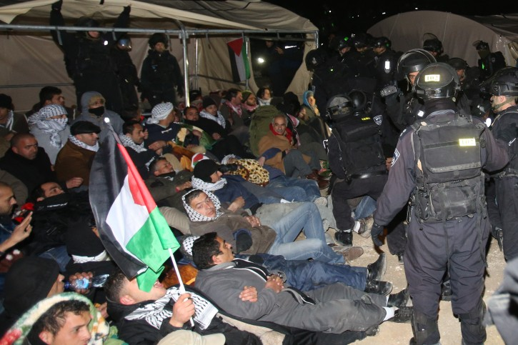 Israeli border police remove a Palestinian from an outpost of tents in an area known as E1, near Jerusalem January 13, 2013. Israeli security forces evacuated about 100 Palestinians early on Sunday from an outpost of tents pitched in an area of the occupied West Bank that Israel has earmarked for a new settlement.  Photo by  FLASH90