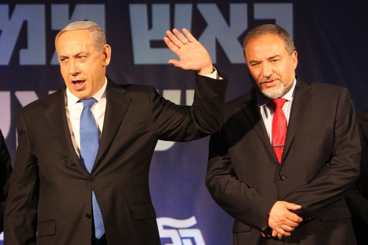 Head of the Likud party ans Israel's Prime Minister Benjamin Netanyahu and leader of the Israel Beiteinu party Avigdor Liberman wave to supporters after the exit polls in the general elections were announced leaving the Liku-Israel Beiteinu party as the largest faction in Israel's 19th parliamentary race.  January 22, 2013. Photo by miriam Alster/FLASH90