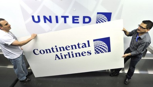 AP FILE - Rich Accordino, left, and Juan Perez-Wheeler remove an old Continental Airlines sign to reveal the new United Airlines logo featuring Continental's globe