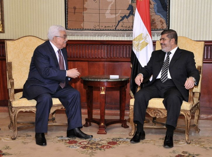 In this photo released by the Egyptian Presidency, Palestinian President Mahmoud Abbas, left, talks with Egyptian President Mohammed Morsi during a photo opportunity following Abbas' arrival in Cairo, Egypt, for the Organization of Islamic Cooperation summit, Tuesday, Feb. 5, 2013. (AP Photo/Egyptian Presidency)