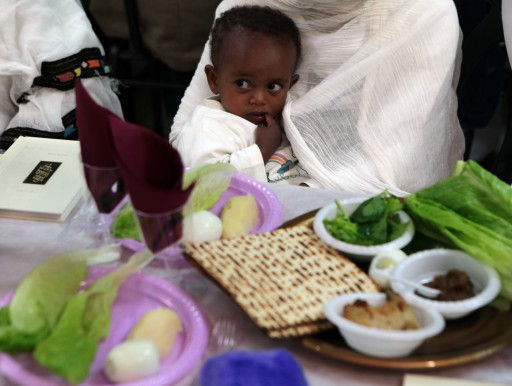 A young Ethiopian immigrant girl holds her mother's robes at the rehearsal of a Passover 'Seder' meal in the absorption center in Mevesseret Zion, outside of Jerusalem on 14 April 2011. EPA/JIM HOLLANDER
