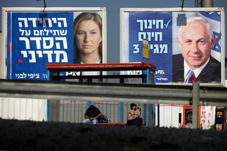 People wait at a bus stop near billboards of Benjamin Netanyahu (R) and Tzipi Livni (L), in Tel Aviv, Israel, 20 January 2013. EPA/ABIR SULTAN