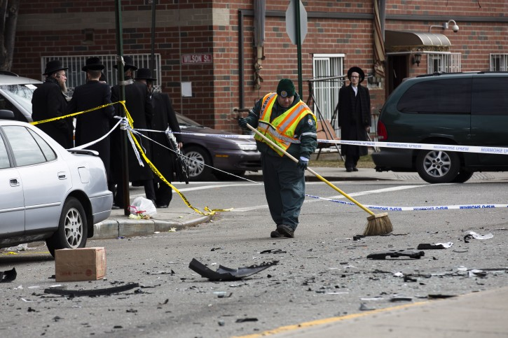 A worker clears debris  from a fatal accident that claimed the lives of two expectant parents, Sunday, March 3, 2013, in the Brooklyn borough of New York. A driver struck the car the couple were riding in early Sunday morning, killing both parents while their baby, whowas born prematurely, survivedand isin critical condition. (AP Photo/John Minchillo)