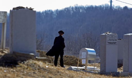 A person walks towards the graves of Nathan and Raizy Glauber, at the Satmar Cemetery 2 in Kiryas Joel, New York, Monday, March 4, 2013. (AP Photo/Craig Ruttle)