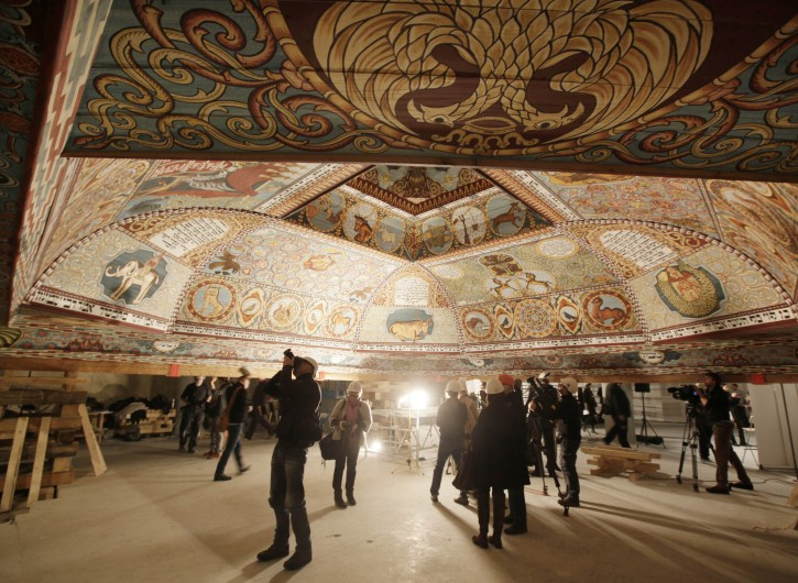 People look at the the painted ceiling of a reconstructed wooden synagogue that dates back centuries during a presentation to the media in Warsaw, Poland, on Tuesday March 12, 2013. The reconstructed ceiling and roof of the 17th century synagogue is a key attraction in the Museum of the History of Polish Jews, a major institution due to open next year in Warsaw.(AP Photo/Czarek Sokolowski)