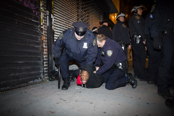 Police officers arrest a demonstrator during a march after a vigil held for Kimani Kiki Gray in the East Flatbush neighborhood of Brooklyn, Wednesday, March 13, 2013. (AP Photo/John Minchillo)
