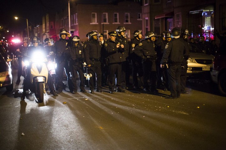 Police officers regroup after a volley of glass bottles are thrown at them from a group of demonstrators during a march following a vigil held for Kimani Kiki Gray in the East Flatbush neighborhood of New York's Brooklyn borough, Wednesday, March 13, 2013. (AP Photo/John Minchillo)