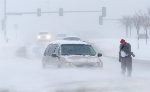 Orlin Wagner / AP<br /> A man waits for help after becoming stuck in snow along West 6th Street in Lawrence, Kan., March 24.