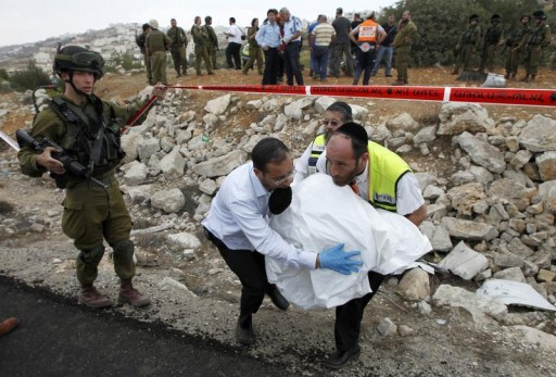 FILE - Members of the Israeli emergency service Zaka carry the body of Yonatan Palmer away from the scene of a car crash near the West Bank city of Hebron September 23, 2011. Reuters