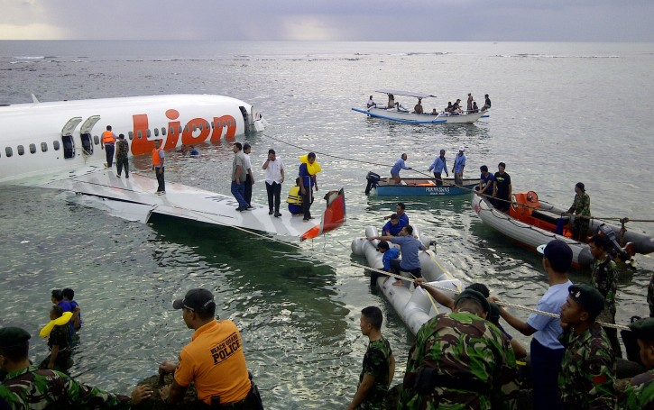 A handout picture provided by the Indonesian Search And Rescue Agency (SAR) shows rescue teams working at the Lion Air plane after it crashed into the water as it overshot the runway at Bali's Ngurah Rai International Airport, Bali, Indonesia, 13 April 2013. EPA/SAR/HO
