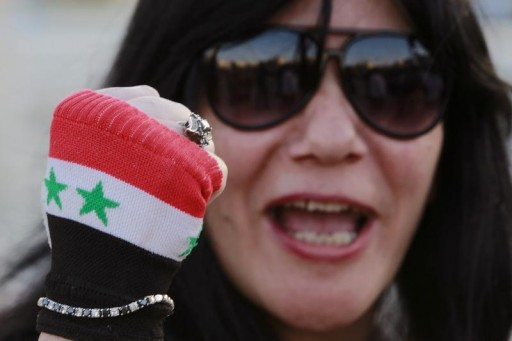 FILE - A Jordanian activist wearing a glove in the colours of the Syrian flag shouts slogans against Israel during a protest to show support to Syria's President Bashar al-Assad and condemning an air strike in Syria, near the Israeli embassy in Amman May 5, 2013.  Reuters
