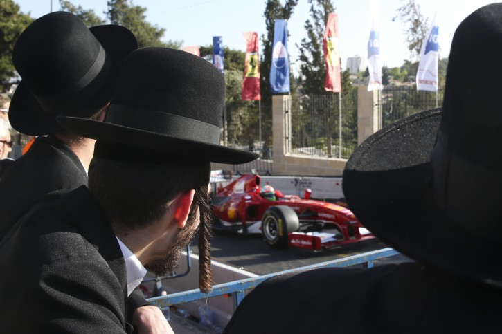 Ultra Orthodox Jews watching Ferrari Formula One racing car during a performance on 13 June 2013 in Jerusalem, Israel, as part of the 'Peace Road Show' event aimed at highlighting peace and coexistence on 13 to 14 June around the Old City of Jerusalem. Photo by Nati Shohat/Flash90
