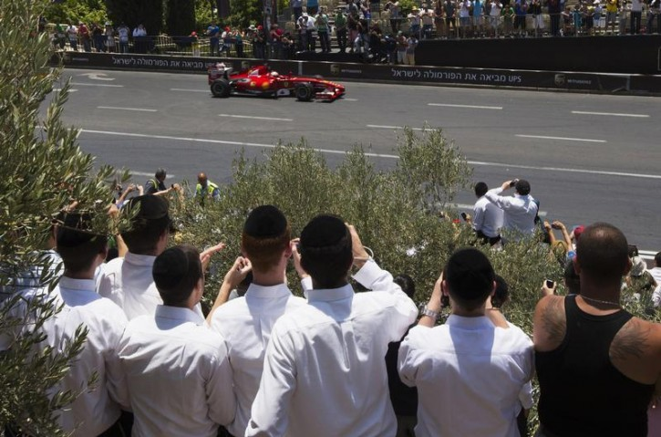 Ultra-Orthodox Jewish youths take photographs of a Ferrari F60 during an road show in Jerusalem June 14, 2013. Organised by the Jerusalem municipality and various sponsors, the first-ever two-day Jerusalem Formula Peace Road Show came to an end on Friday with Formula One racing teams, Scuderia Ferrari and Marussia participating in the show, whose circuit passes landmarks such as Jerusalem's Old City walls. REUTERS/Ronen Zvulun