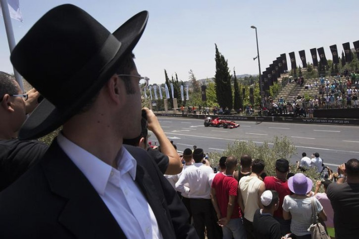 An ultra-Orthodox Jewish youth (L) watches a Ferrari F60 drive past during in a road show in Jerusalem June 14, 2013. Organised by the Jerusalem municipality and various sponsors, the first-ever two-day Jerusalem Formula Peace Road Show came to an end on Friday with Formula One racing teams, Scuderia Ferrari and Marussia participating in the show, whose circuit passes landmarks such as Jerusalem's Old City walls. REUTERS/Ronen Zvulun