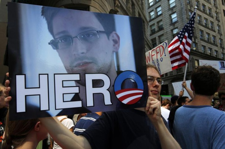 """A demonstrator holds a sign with a photograph of former U.S. spy agency NSA contractor Edward Snowden and the word """"HERO"""" during Fourth of July Independence Day celebrations in Boston, Massachusetts July 4, 2013.  Reuters"""