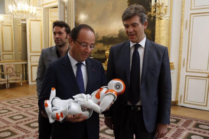 France's President Francois Hollande holds an humanoid robot
