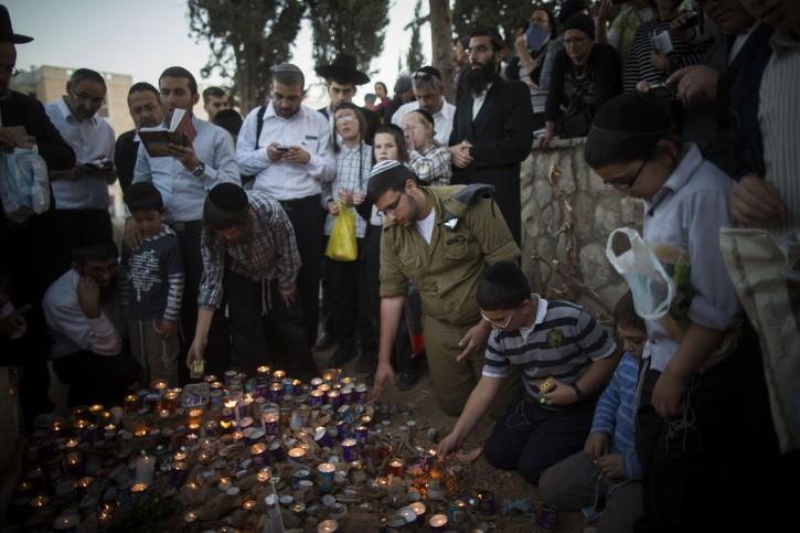 Ultra-Orthodox Jews pray on the grave of Rabbi Ovadia Yosef at the Sanhedriya cemetery in Jerusalem on October 08, 2013. Rabbi Yosef passed away Monday in Jerusalem at the age of 93. Photo by Yonatan Sindel/Flash90