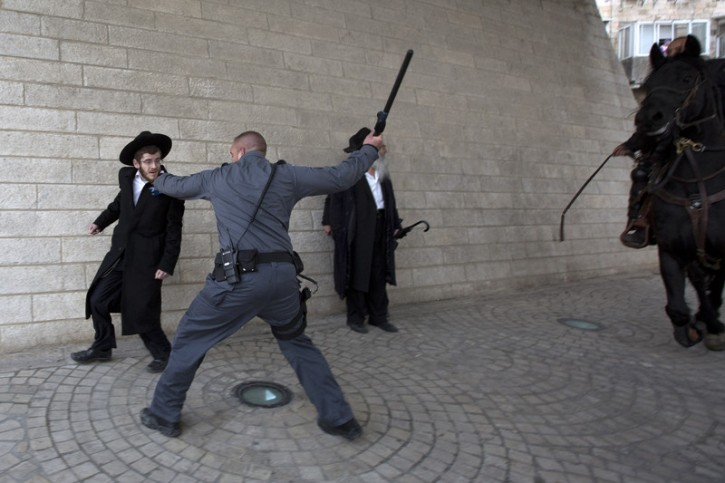 Israeli police uses his club to hit an ultra-Orthodox young man to move him from under a bridge during a large protest by ultra-Orthodox held at the entrance to Jerusalem, 06 February 2014. EPA/JIM HOLLANDER