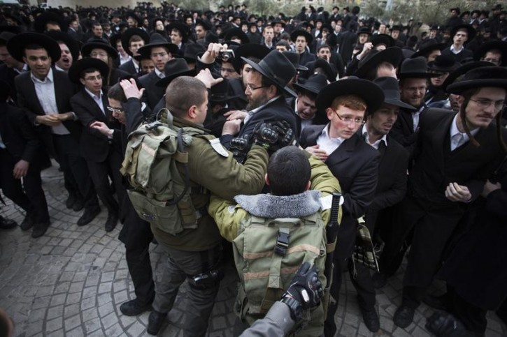 Israeli border policemen scuffle with ultra-Orthodox Jewish protesters during a demonstration in Jerusalem February 6, 2014. Hundreds of ultra-Orthodox Jews in Israel blocked highways and clashed with police on Thursday in protest at a government decision to cut funds to seminary students who avoid military service. REUTERS/Baz Ratner