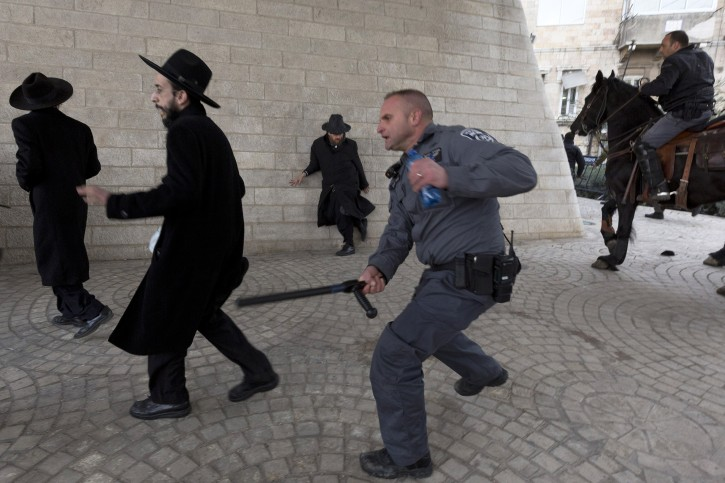 Israeli police uses his club to hit an ultra-Orthodox young man to move him from under a bridge during a large protest by ultra-Orthodox held at the entrance to Jerusalem, 06 February 2014. Several thousand ultra-Orthodox protested in Jerusalem and other Israeli cities and towns after an ultra-Orthodox Jewish young man was arrested when he dodged the draft. Police used water canon and horses (R) and made many arrests in breaking up the protest.  EPA/JIM HOLLANDER