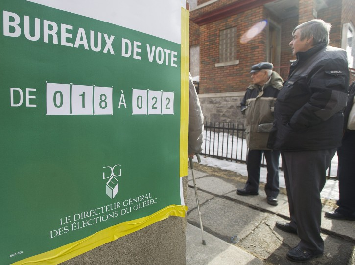 People wait in line to vote at a polling station in Montreal Monday, April 7, 2014 on election day in Quebec. (AP Photo/The Canadian Press, Graham Hughes)
