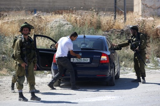 Israeli soldiers stops a Palestinian for a security check during a military operation to search for three missing Israeli teenagers near the West Bank city of Hebron, 15 June 2014. EPA/ABIR SULTAN