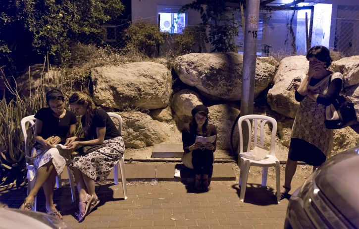Young Israeli women sit and read prayers outside outside the home of missing 16-years ol Natfali Frenkel, after hearing the news of Naftali and the two other teenager's Israelis bodies discovered earlier, in a pit in the West Bank village of Halhoul, near Hebron, in Nof Ayalon, Israel, 30 June 2014. EPA