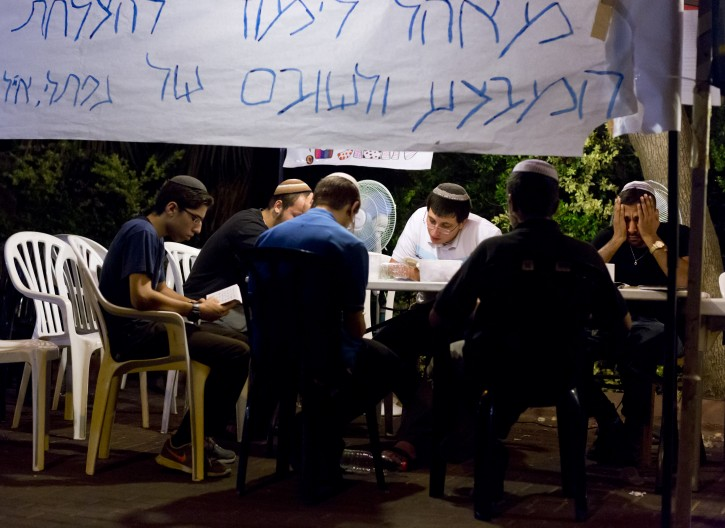 oung Israelis men sit under a tent to recite prayers outside the home of missing 16-years ol Natfali Frenkel, after hearing the news of Naftali and the two other teenager's Israelis bodies discovered earlier, in a pit in the West Bank village of Halhoul, near Hebron, in Nof Ayalon, Israel, 30 June 2014. EPA
