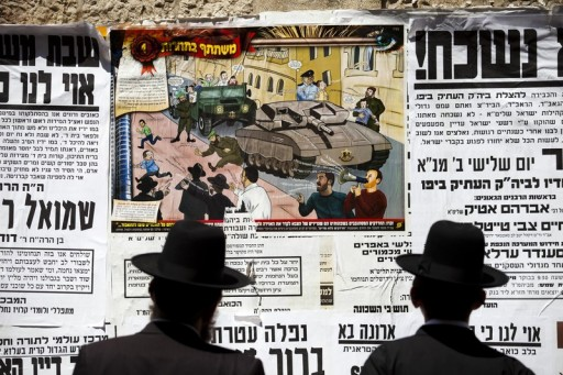 File Photo: Ultra-Orthodox Jews look at a poster with a cartoon depicting Israeli soldiers pursuing Ultra Orthodox Jewish children.  EPA/ABIR SULTAN