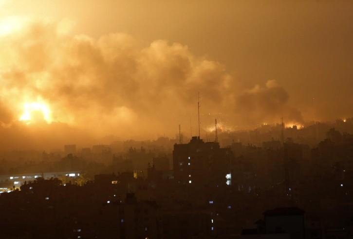 Smoke rises as flames spread across buildings after Israeli strikes in the Shijaiyah neighborhood in Gaza City, Tuesday, July 22, 2014. (AP Photo/Khalil Hamra)