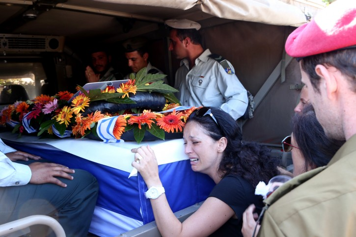 Wife of IDF (Isreal Defense Force) reservist Yair Ashkenazi, seen crying on the coffin carrying her husband, at Ashkenazi's funeral, at the military cemetery in Rehovot on July 25, 2014. Ashkenazi, a combat soldier in a reserve brigade, was killed during combat in the northern Gaza Strip. Photo by FLASH90