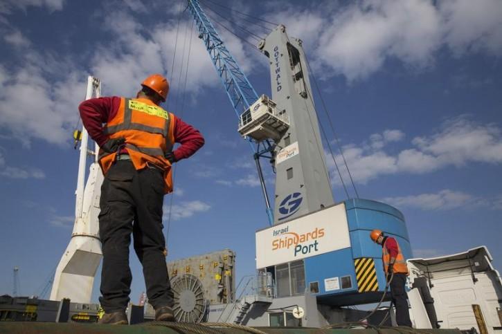 Workers load trucks at Israel Shipyards Port in Haifa February 5, 2014. Reuters