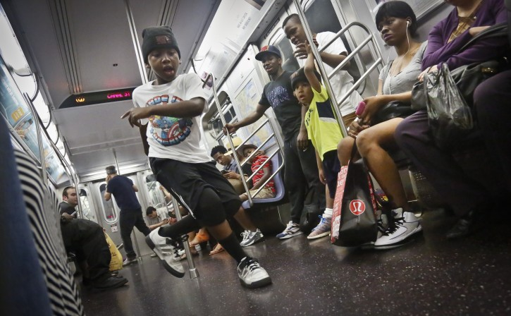 """In this June 17, 2014 photo, Marc Mack, 8, a member with the dance troupe W.A.F.F.L.E., performs on a subway, in New York. Police Commissioner William Bratton's department """"broken window"""" crackdown has targeted illegal motorcycles, graffiti and the subway acrobats. (AP Photo/Bebeto Matthews)"""