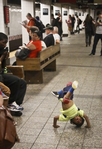 In this June 17, 2014 photo, acrobatic dancer Nasir Malave, 5, works through a routine on a subway platform in New York. Malave performs with the dance troupe W.A.F.F.L.E. Though no injuries have been reported, police insist the showmanship is a safety issue. (AP Photo/Bebeto Matthews)