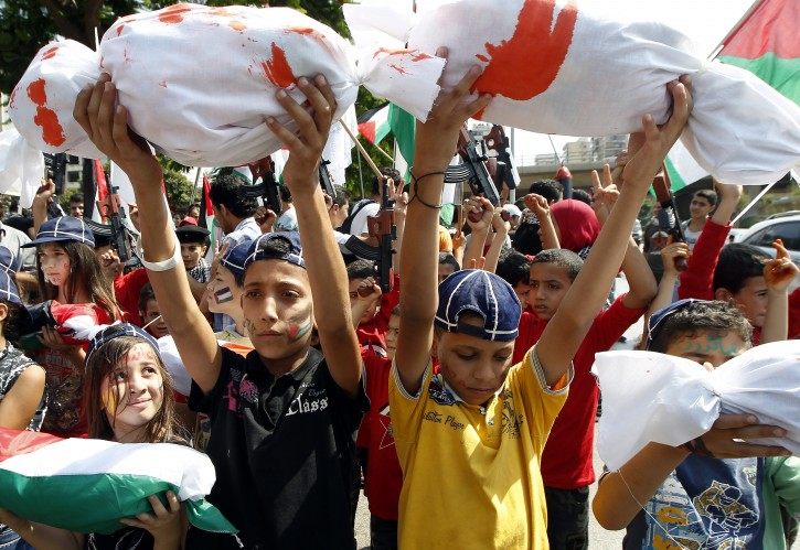 Palestinian supporters of the Palestinian Democratic Youth Union hold up bundles representing children dead as a result of the conflict in Gaza, while others wave Palestinian flags and toy guns, during a protest against violence against Palestinian children in the context of the Palestinian-Israeli conflict, in front of the UN building in Beirut, Lebanon, 21 July 2014.  EPA