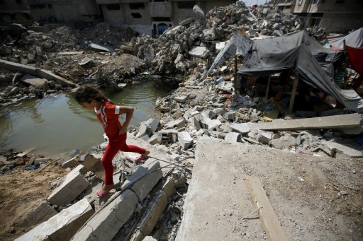A Palestinian girl walks amid the rubble of her desroyed house in Al Shejaeiya neighbourhood in the east of Gaza City, 28 August 2014. EPA/MOHAMMED SABER