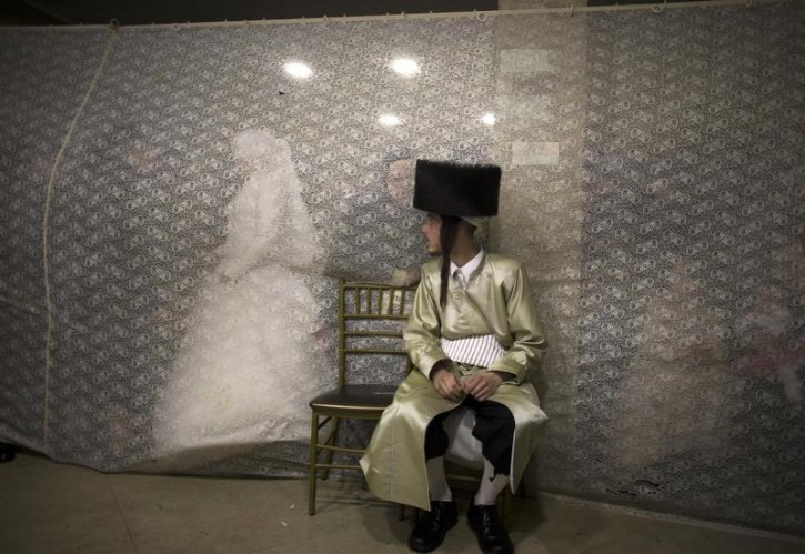 Ironically VINnews has found that Reuters has covered the same wedding showing in this image Rivka Krauss walking behind a curtain towards her groom Aaron Krauss (front) after their traditional wedding ceremony in the Mea Shearim neighbourhood of Jerusalem February 18, 2014. (REUTERS/Ronen Zvulun )