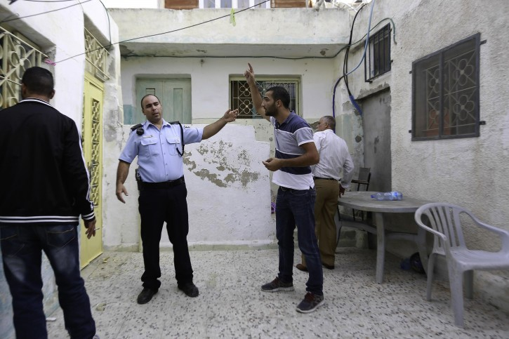 In this photo taken Tuesday, Sept. 30, 2014, Palestinian Mahmoud Qarain, a 30-year-old resident of the east Jerusalem neighborhood of Silwan, argues with Israeli police inside his cousin's home, which has been taken over by Jewish settlers. (AP Photo/Mahmoud Illean)