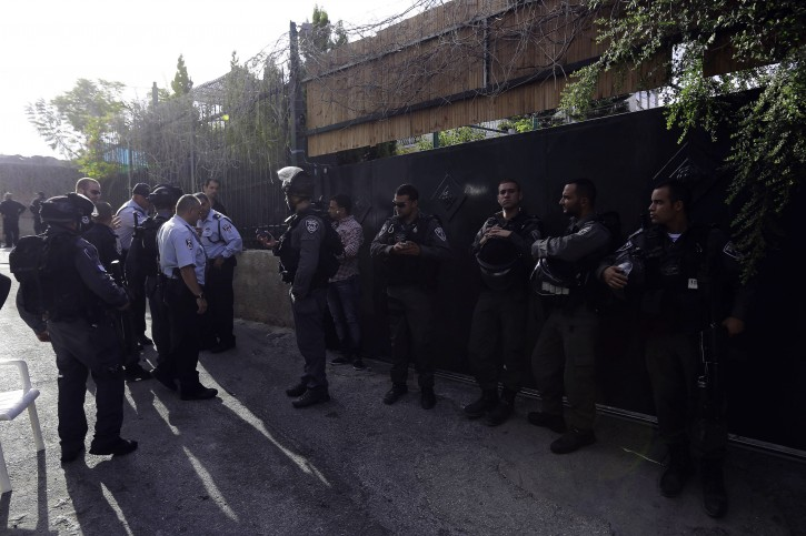 In this photo taken Tuesday, Sept. 30, 2014, Israeli police officers guard the house of Ziad Qarain, that Jewish settlers moved into, at the Palestinian neighborhood of Silwan, East Jerusalem. (AP Photo/Mahmoud Illean)