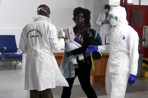 FILE - Kenyan Port Health Services workers wearing protective equipment receive a woman and her child prior to their Ebola screening as they arrive from Ebola hit Liberia, at Jomo Kenyatta International Airport (JKIA) in Nairobi, Kenya, 28 October 2014. EPA