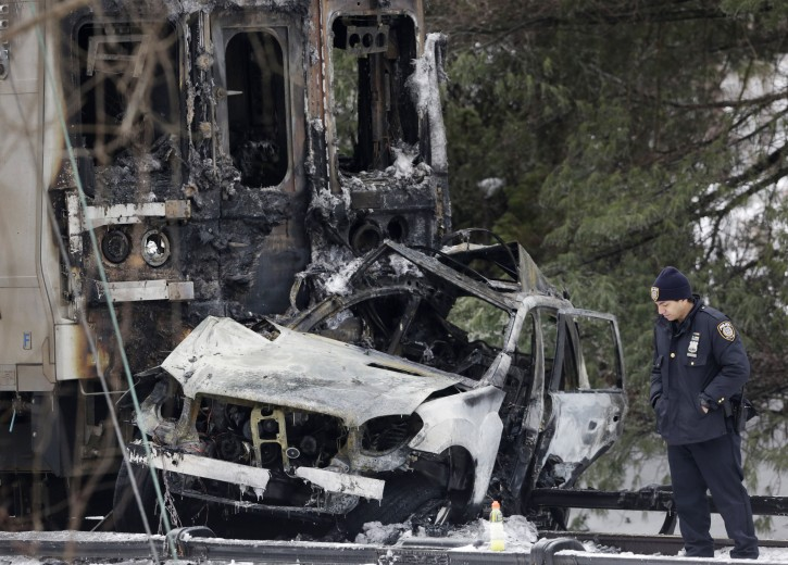 A police officer looks at an SUV that was crushed at the front of a Metro-North Railroad train Wednesday, Feb. 4, 2015, in Valhalla, N.Y. AP