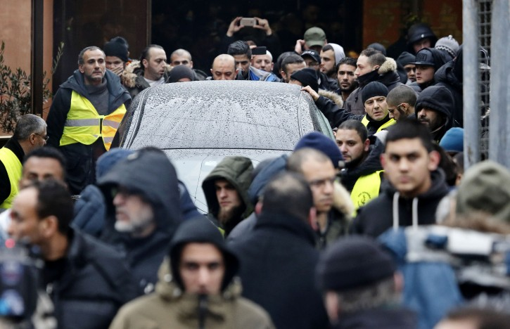 The car containing the body of Omar Abdel Hamid El-Hussein, the man accused of the two shootings which led to two civilians dead last weekend in Copenhagen, is escorted from the Islamic Society's building in Copenhagen, Friday, Feb. 20, 2015, to a Muslim burial ground in Brondby, west of Copenhagen. He was shot by police Sunday morning outside his home. (AP Photo/Polfoto, Jens Dresling)