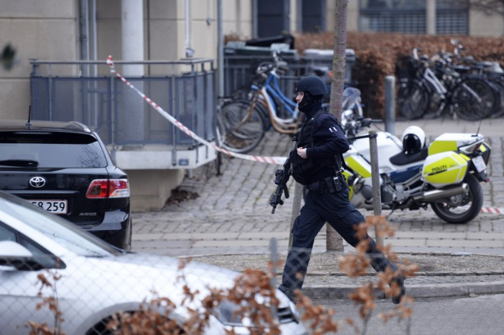 """An armed security officer runs down a street near a venue after shots were fired where an event titled  """"Art, blasphemy and the freedom of expression"""" was being held in Copenhagen, Saturday, Feb. 14, 2015. AP"""