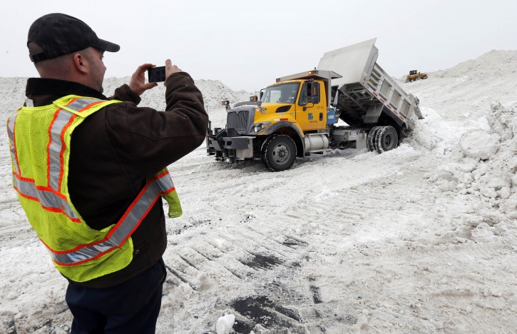 """Rick Chestnet, who works for the Pennsylvania Department of Transportation,  records a video on his cell phone as a department truck unloads snow at a """"snow farm"""" in Boston, Saturday, Feb. 14, 2015. Crews from around the region have worked urgently to remove the massive amounts of snow that has clogged streets and triggered numerous roof collapses ahead of yet another winter storm due to arrive on Saturday. (AP Photo/Michael Dwyer)"""