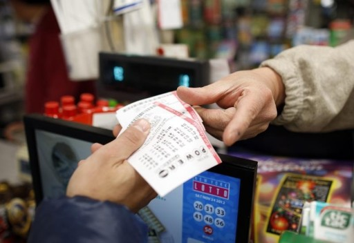 FILE - A customer buys tickets for the PowerBall lottery in New York, November 28, 2012. REUTERS