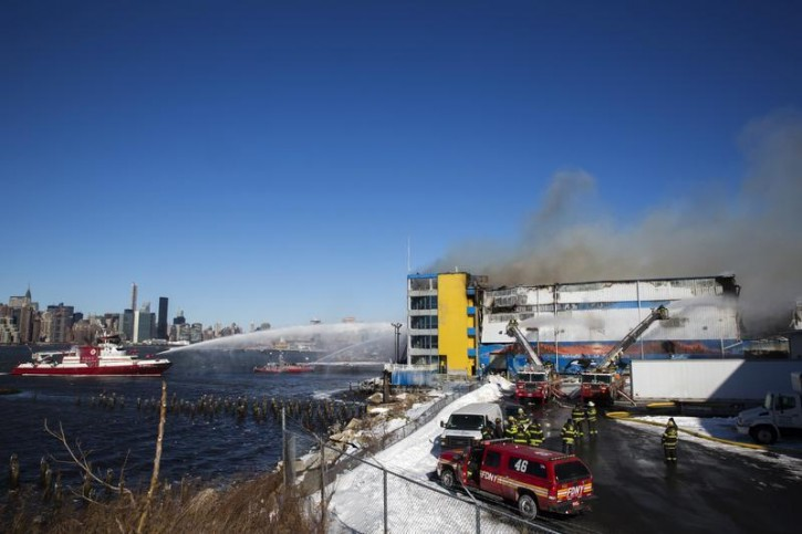Members of the New York Fire Department battle a six alarm fire in a storage facility on the waterfront of the East River in New York January 31, 2015. REUTERS/Lucas Jackson