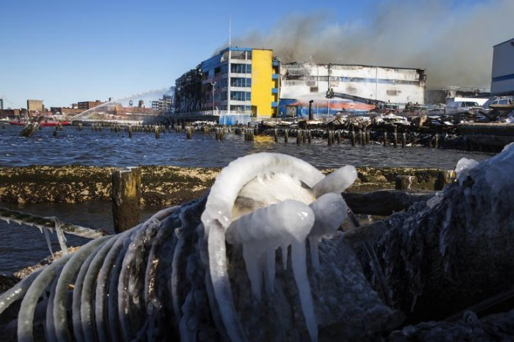 Members of the New York Fire Department battled a six alarm fire in a storage facility on the waterfront of the East River in New York January 31, 2015. REUTERS/Lucas Jackson