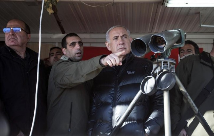 Israel's Prime Minister Benjamin Netanyahu (C) and Defence Minister Moshe Yaalon, stand next to Israeli soldiers at a military outpost during a visit to Mount Hermon in the Golan Heights over looking the Israel-Syria border February 4, 2015. REUTERS/Baz Ratner