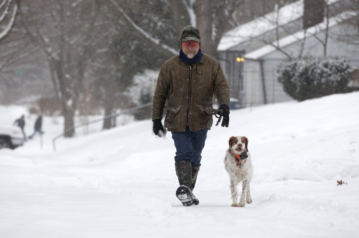 Dana Farrell walks his dog Woody after more than 2 inches of snow fell in Ann Arbor, Mich., Sunday, Feb. 1, 2015. Farrell said the snow slowed him down a little bit in the morning, but that it was expected. (AP Photo/The Ann Arbor News, Patrick Record)